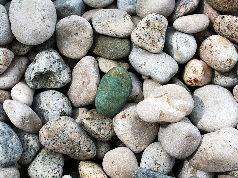Beach Gravel Texture. Closeup of gravel-stones on the beach shore forming natural texture. Pebble rocks has light-gray color with one dark green one in the royalty free stock images