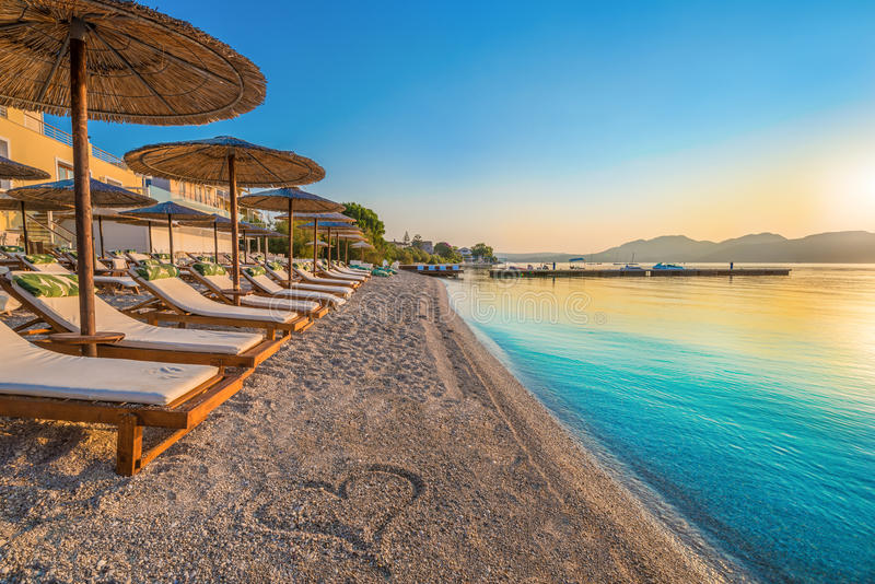 Beach, Greece. Beautiful view over the beach Nikiana with chairs, umbrellas and a heart drawing on sand, in Lefkada island, Greece royalty free stock photo