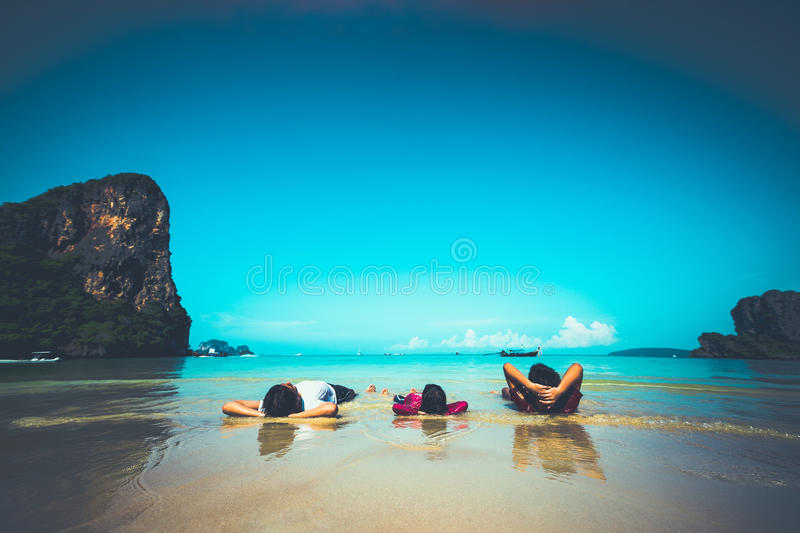 On the beach. Happy child on tropical beach laying on sand stock image