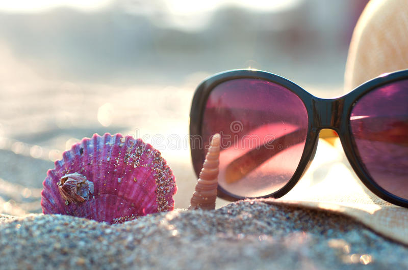 Beach hat and sunglasses. On a beach with seashells stock photo