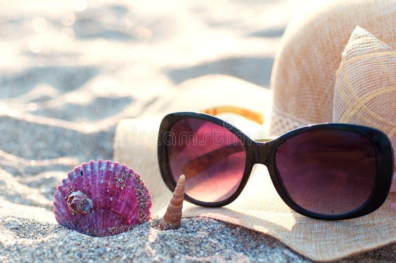 Beach hat and sunglasses. On a beach with seashells stock photos
