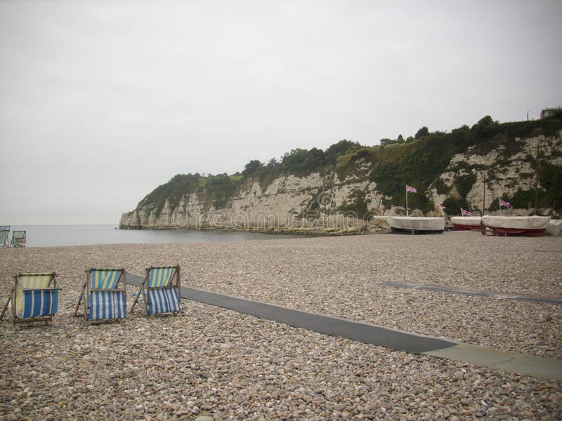 Deckchairs on beach. Beach with headland and three deckchairs facing the sea. Sky is grey and the sea is calm royalty free stock photography