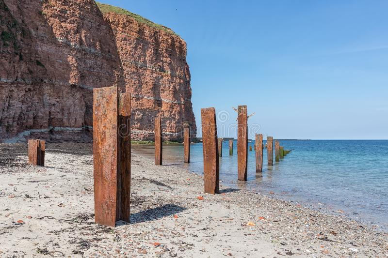 Beach Helgoland island with red cliffs and rusty iron pillars. Of old putrefied jetty royalty free stock photography