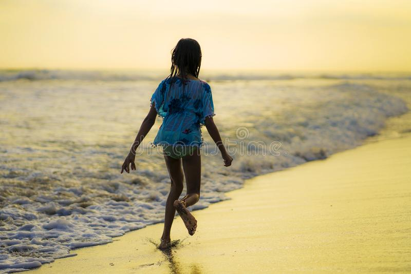 Beach holidays lifestyle portrait of young happy and excited child girl running in the beach feeling free having fun playing stock image