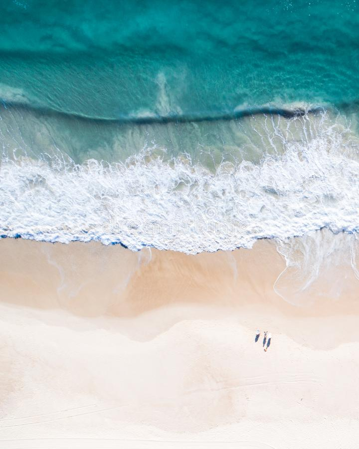 Beach aerial view on the Gold Coast. Nice top view of the blue ocean, crashing wave, white sand and people enjoying a walk. stock image
