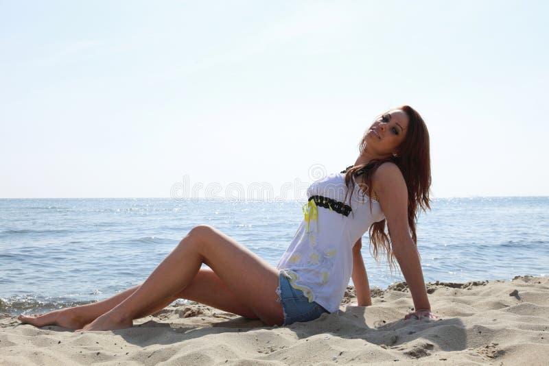 Beach holidays woman enjoying summer sun sand looking happy. Beach holidays woman enjoying summer sun lie in sand looking happy at copy space. Beautiful young stock image