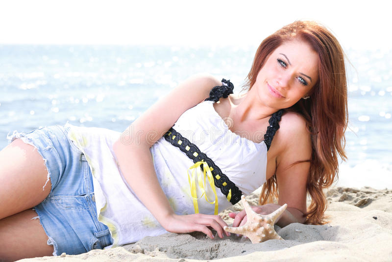 Beach holidays woman enjoying summer sun sand looking happy. Beach holidays woman enjoying summer sun lie in sand looking happy at copy space. Beautiful young royalty free stock image
