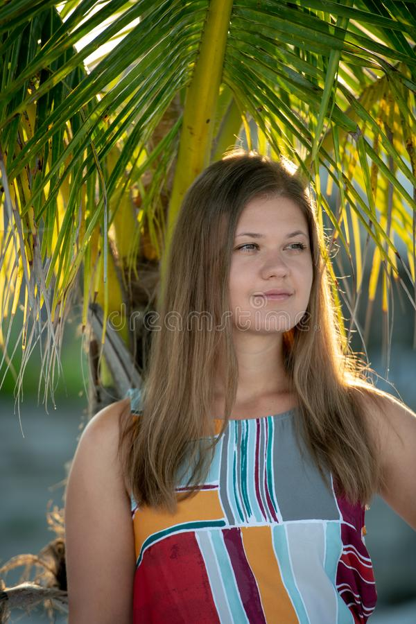 Close-up of sensual young woman with palm tree. Beach holidays woman wearing dress smiling on tropical beach summer vacation with palm trees stock images