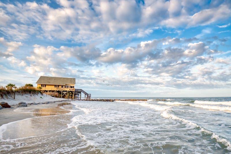 A beach house on stilts over the beach. A beach house on stilts over the beach with a blue cloudy sky royalty free stock photos