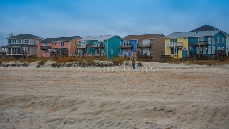 Beach houses with sand and grass and storm clouds royalty free stock photography
