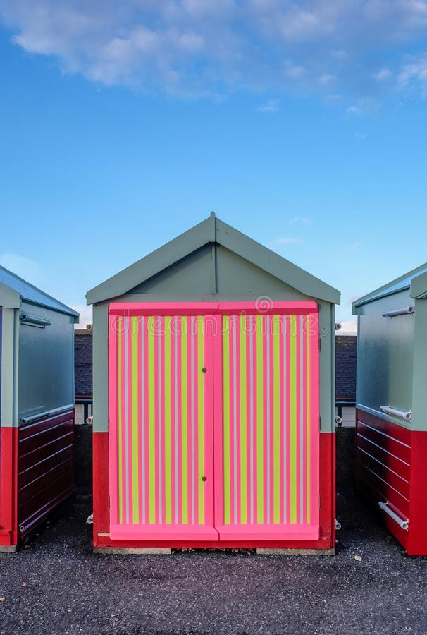 A beach hut with a multi coloured door, stripey yellow, pink, co stock photos