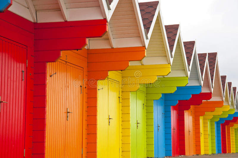 Beach huts. Colourful row of wooden beach huts stock images