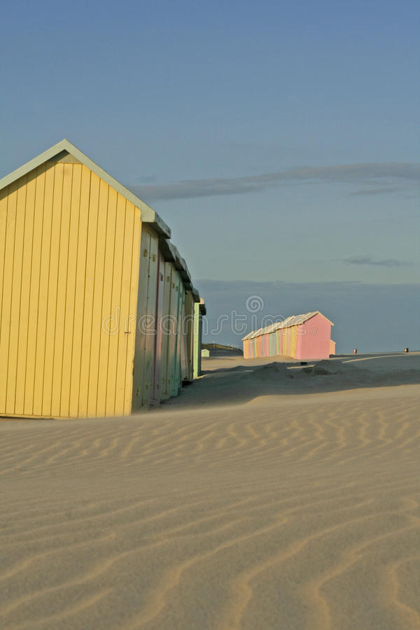 Beach huts. Brightly colored beach huts with patterned sand and blue sky royalty free stock images
