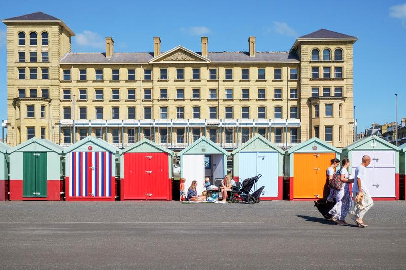 Beach huts and buildings on Brighton promenade. Brighton, East Sussex, United Kingdom, UK - September 13, 2019 : A line of colourful beach huts with a family stock images
