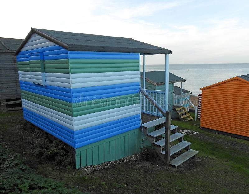 Beach huts chalets sheds in a row by the coast. Photo of a row of wooden beach huts chalets and sheds dotted along the kent coast of whitstable november 2018 stock photography