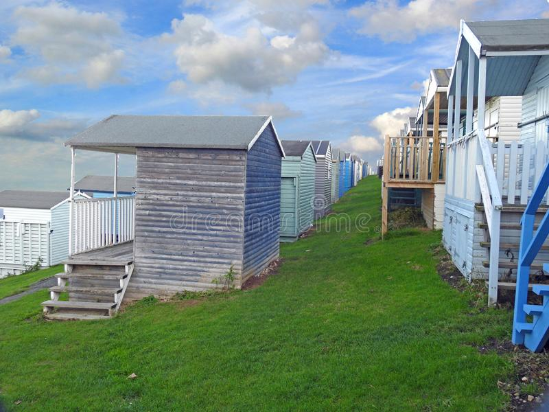 Beach huts chalets sheds in a row by the coast. Photo of a row of wooden beach huts chalets and sheds dotted along the kent coast of whitstable november 2018 stock image