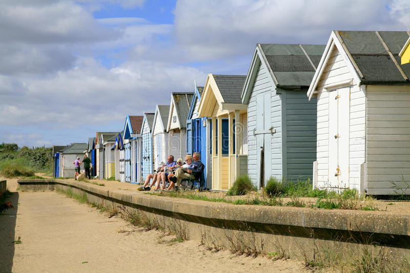 Beach Huts. CHAPEL ST. LEONARDS, LINCOLNSHIRE, UK. AUGUST 04, 2015. Families enjoying the sunshine at the front of the beach huts at Chapel St. Leonards in royalty free stock photo