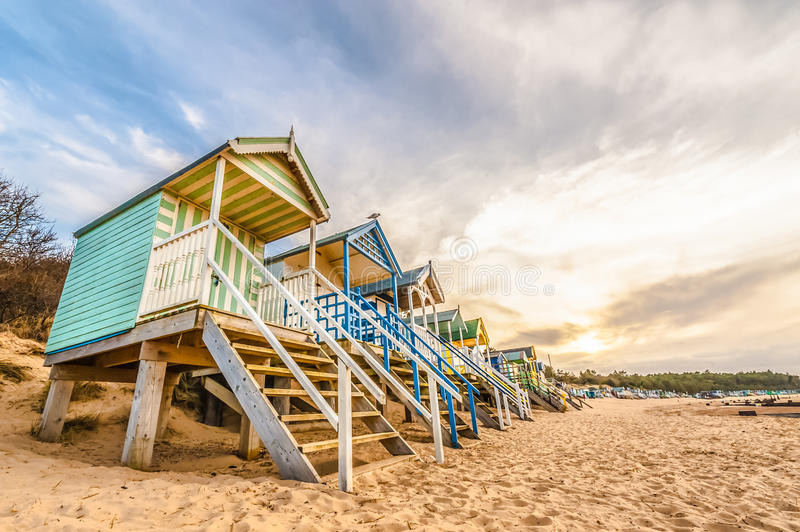 Beach huts. Long line of colorful beach huts at sunset stock photo