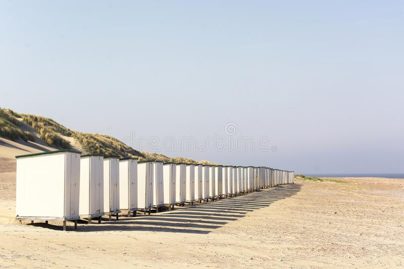 Row of white beach huts on an empty sunny beach in the province of Zeeland, the Netherlands royalty free stock photography