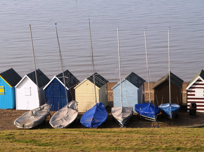 Beach huts and sailing Boats stock images