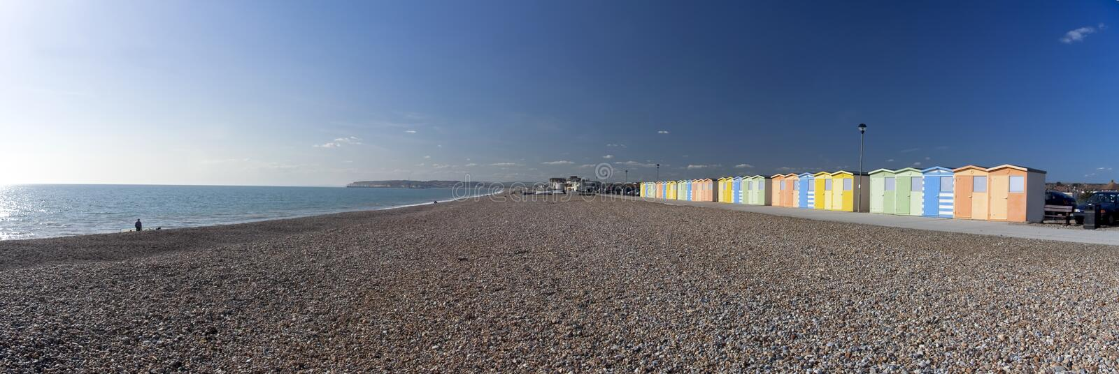 Beach huts seaford head sussex england. Panoramic image of the beach at seaford head near newhaven in east sussex with row of colorful beach huts royalty free stock photography