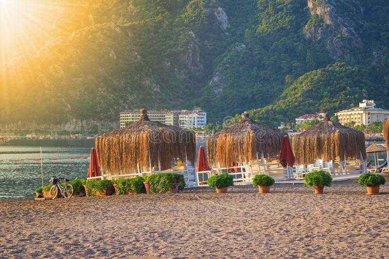 Beach of Icmeler. Empty morning beach of Icmeler, near Marmaris, waiting for tourists. Neatly arranged flower pots by the covered local cafes, Turkey stock images