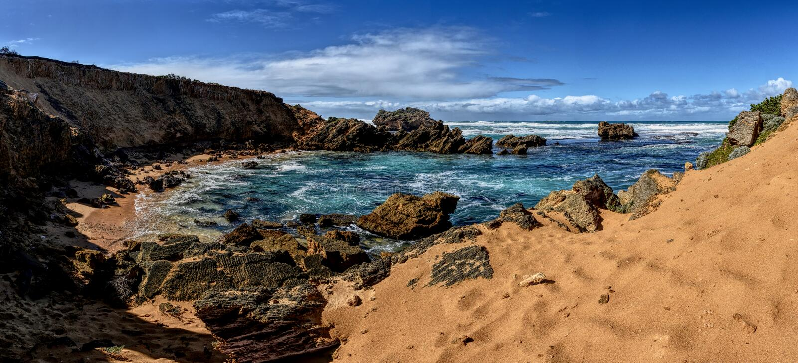 Beach jagged rocks and stones. Swirling ocean water. Cloudy sky. Jaggy scraggy uneven rough gnawed coarse royalty free stock images