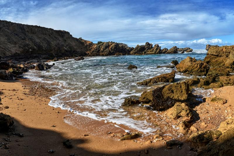 Beach jagged rocks and stones. Swirling ocean water. Cloudy sky. Jaggy scraggy uneven rough gnawed coarse stock image