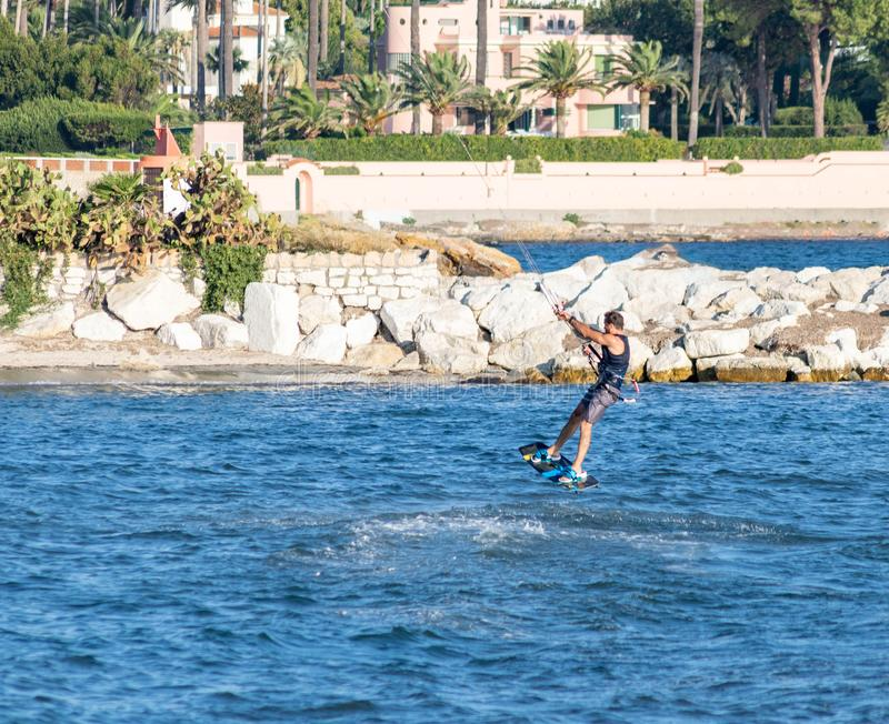 Beach Juan les Pins, French Riviera, France, Kitesurfeur flying above the waves royalty free stock photo