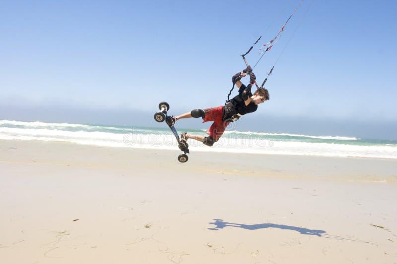 Beach Kiteboarding. Young man kiteboarding on the beach stock image