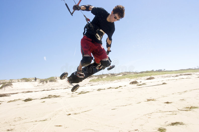 Beach Kiteboarding. Young man kiteboarding on the beach royalty free stock photography