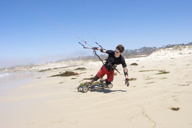 Beach Kiteboarding. Young man kiteboarding on the beach royalty free stock image