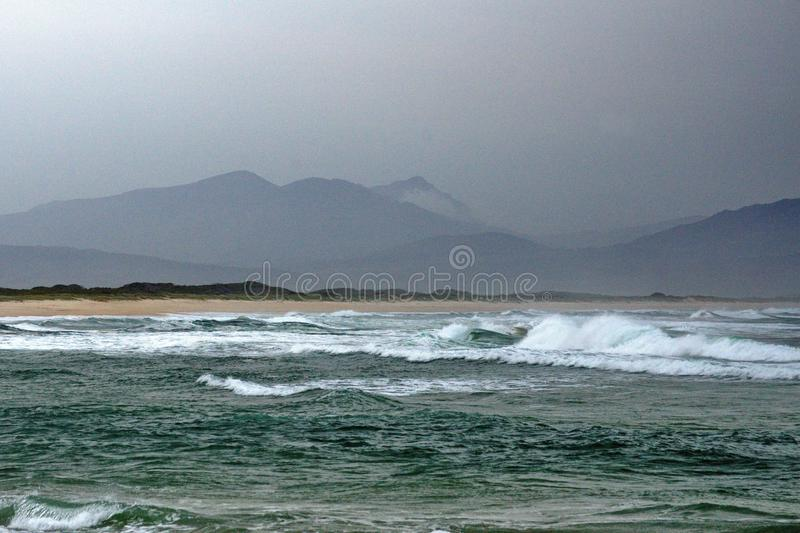 Beach in Kleinmond, South Africa. Beach on a stormy day in Kleinmond, South Africa, with a mountain in the background royalty free stock photography