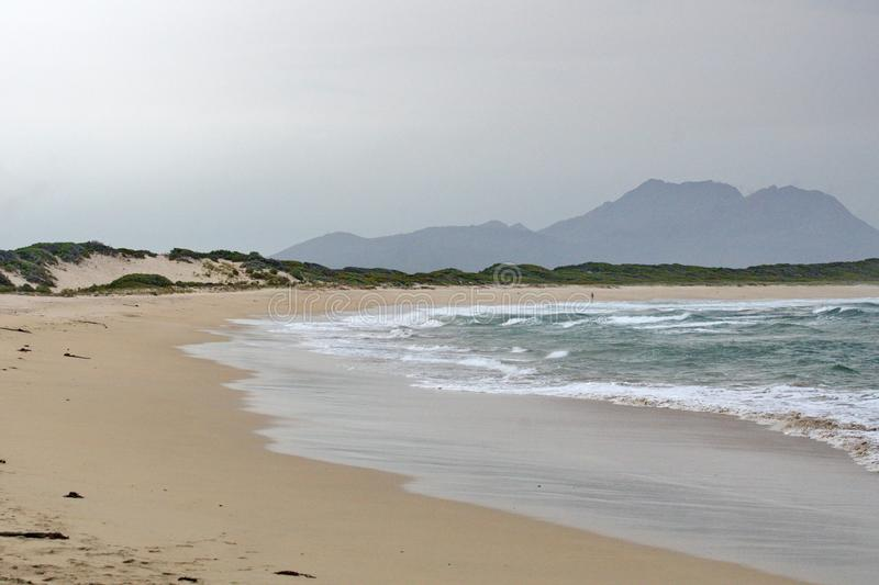 Beach in Kleinmond, South Africa. Beach on a stormy day in Kleinmond, South Africa, with a mountain in the background royalty free stock photos