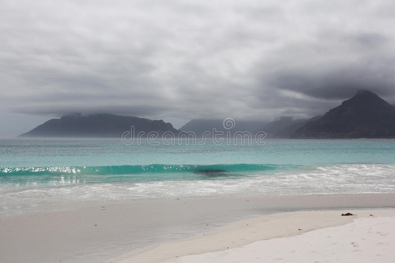 Beach of Kommetjie. With an upcoming storm in the background and blue water stock images
