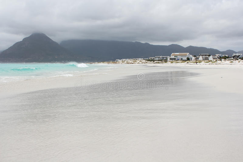 Beach of Kommetjie. With an upcoming storm in the background and blue water royalty free stock images