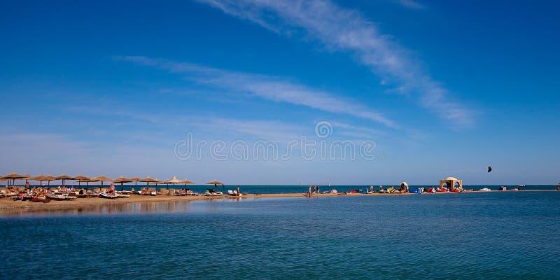 Beach, lagoon and palm huts royalty free stock photo