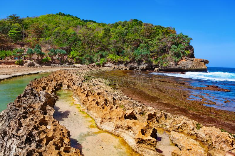 Beach lagoon separated from sea surf by reef barrier. Popular travel destination in East Java - Pantai Batu Bengkung beach with calm water lagoon separated from stock image