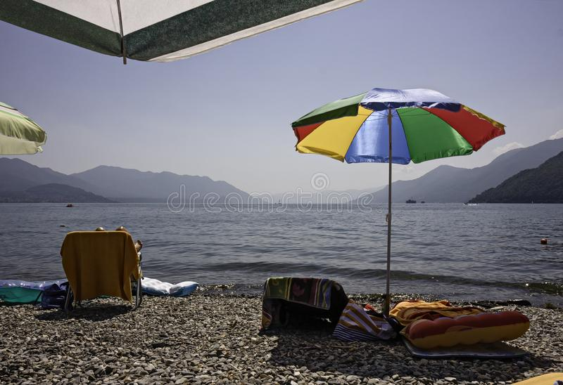 A beach of the lake with sunshades and deckchairs, and inflatable mattresses. stock photography