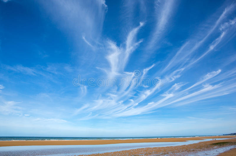 Beach and blue sky with clouds. Beach view during the tide with cirrus clouds above royalty free stock images