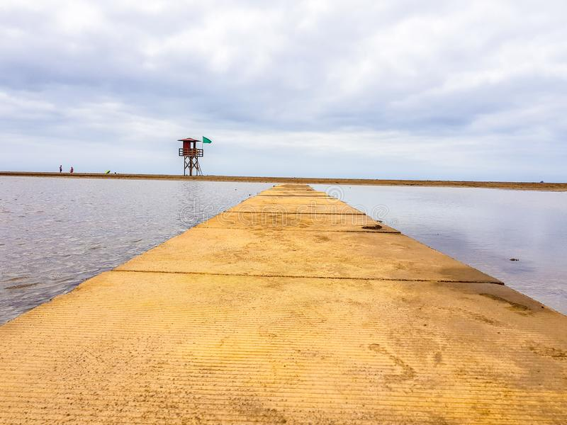 Beach landscape and wooden footbridge to reach the coast with lifeguard post and green flag allowing swimming. Canary Islands,. Spain water tracks morning wet royalty free stock photography