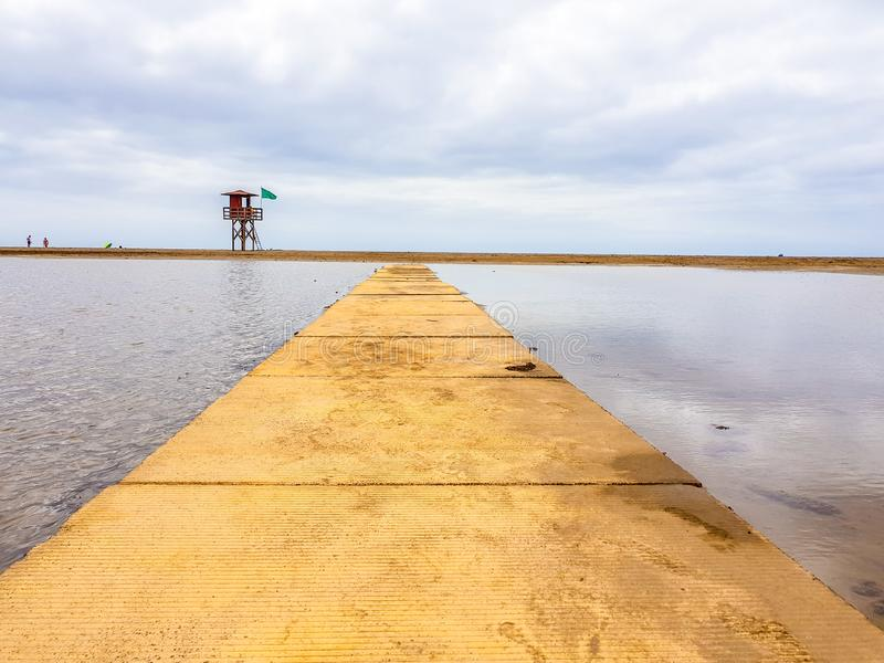 Beach landscape and wooden footbridge to reach the coast with lifeguard post and green flag allowing swimming. Canary Islands,. Spain water tracks morning wet royalty free stock image