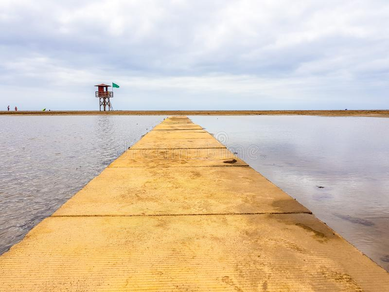 Beach landscape and wooden footbridge to reach the coast with lifeguard post and green flag allowing swimming. Canary Islands,. Spain water tracks morning wet royalty free stock images