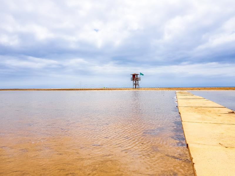 Beach landscape and wooden footbridge to reach the coast with lifeguard post and green flag allowing swimming. Canary Islands,. Spain water tracks morning wet stock image