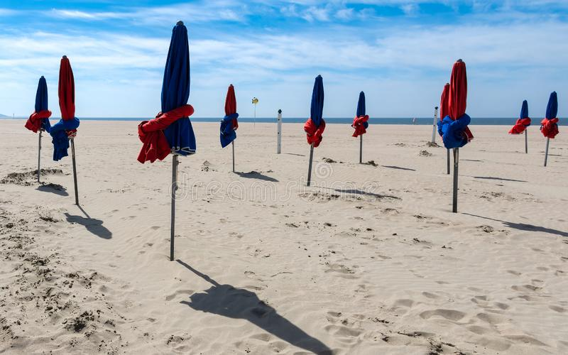 The beach of Les Planches in Deauville in Normandy in France. Closed parasols on the beach of Planches in Deauville in Normandy in France royalty free stock image