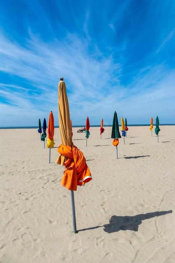 The beach of Les Planches in Deauville in Normandy in France. Closed parasols on the beach of Planches in Deauville in Normandy in France royalty free stock photos