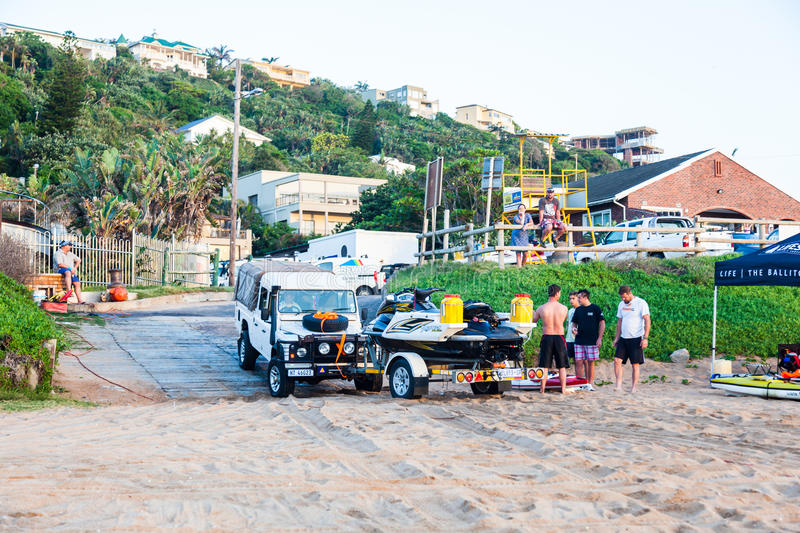 Beach Life. A 4x4 vehicle drives onto the beach with a jetski and trailer to load the ski into the sea. Ballito beach, South Africa stock photo