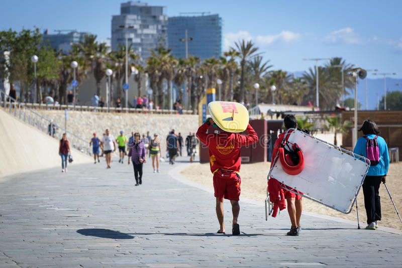 Beach lifeguard men are walking along the promenade of Barceloneta beach stock photo