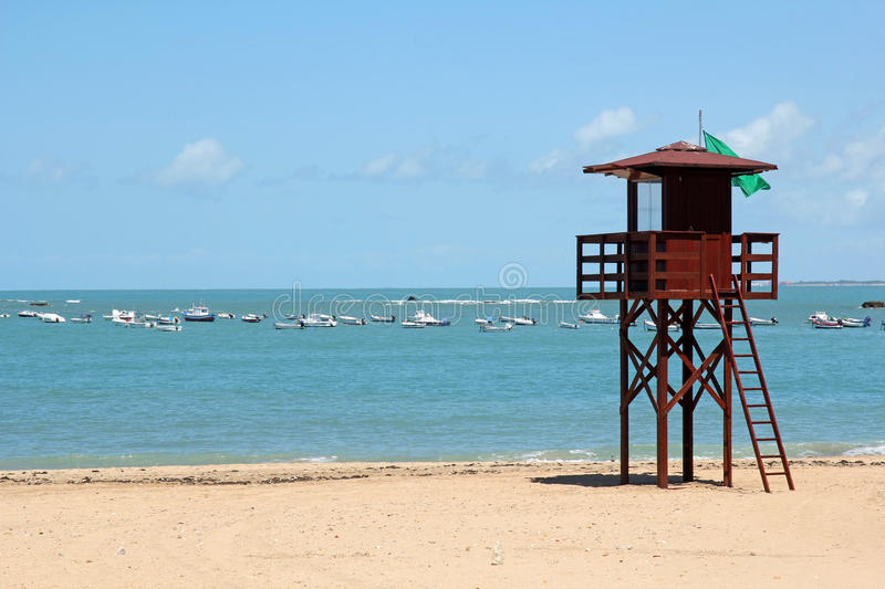 Beach with lifeguard post. And fishing boats in the background royalty free stock image