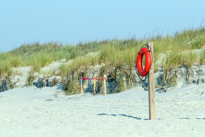 Beach lifeguard rescue equipment on the sand dunes royalty free stock photos